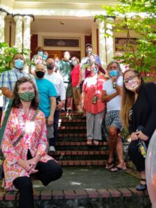 Large group of family and historians in front of Darcelle XV's house in 2020.  All wearing masks.