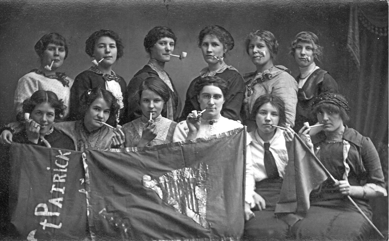 A dozen women with tobacco pipes in their mouths holding up a banner that says St Patrick and has a harp on it. Very silly poses but not a candid image.