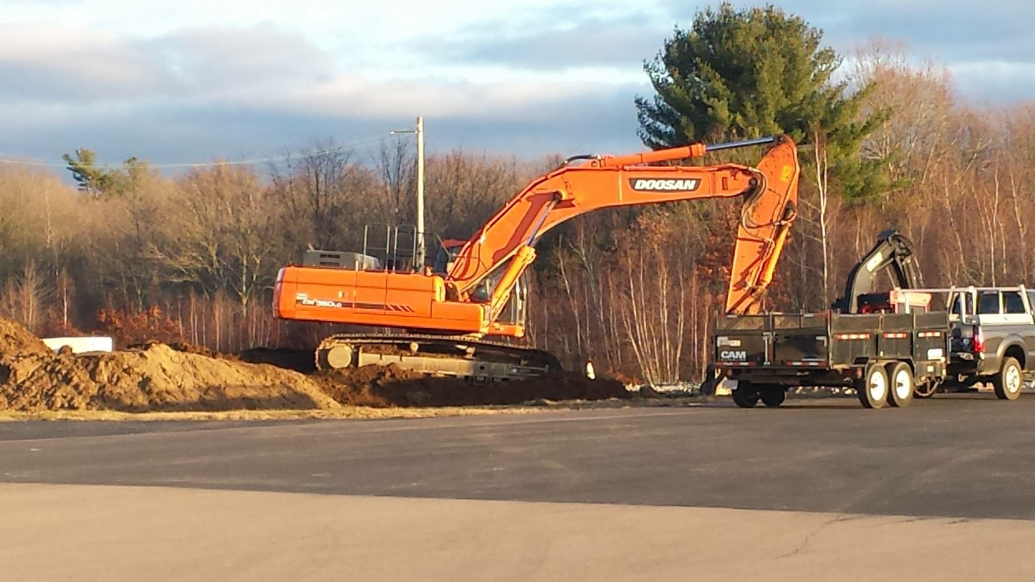 Orange excavator near construction trucks