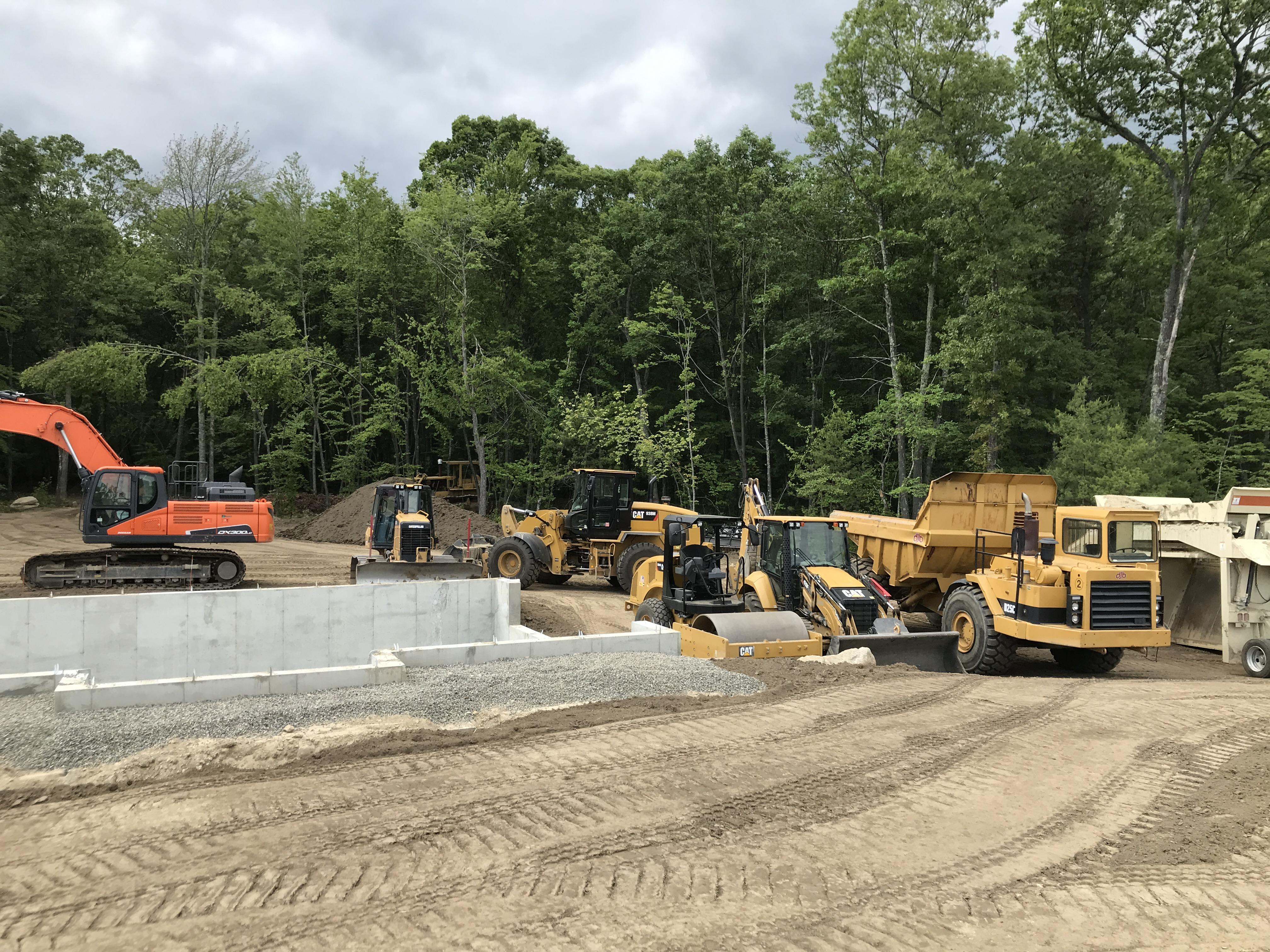 Six construction equipment trucks working on a construction site