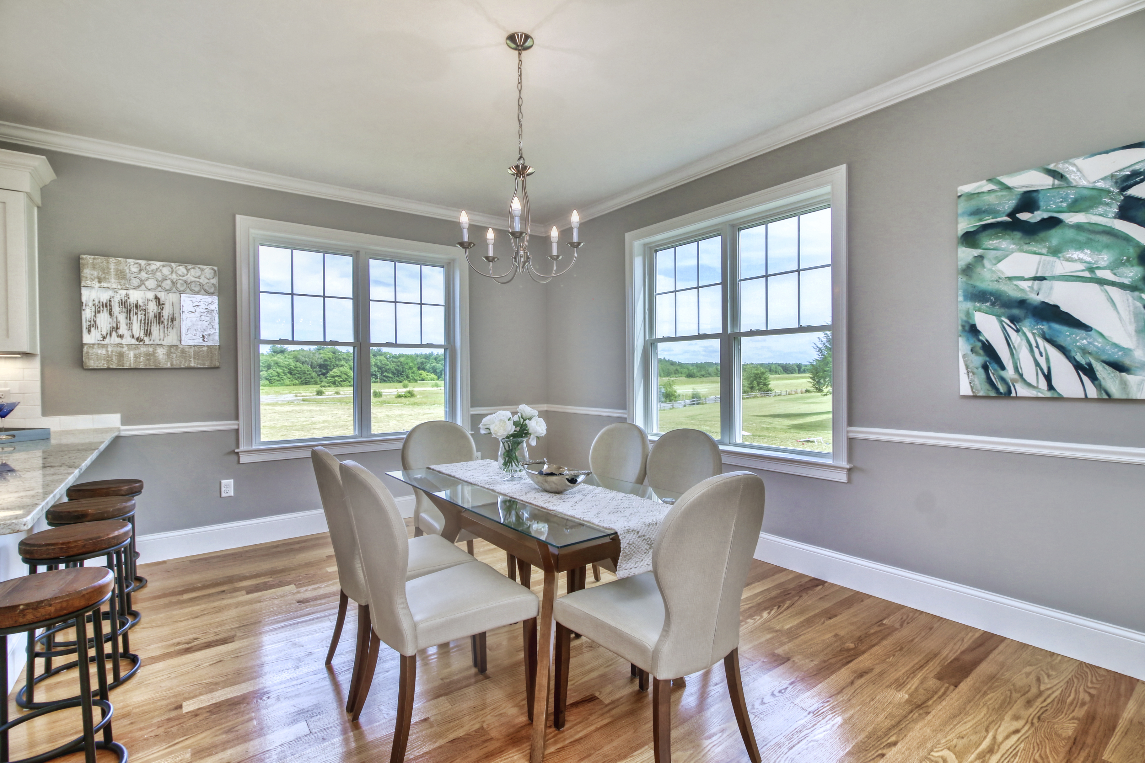 Pastel grey dining room with a dining set and a counter top with barstools