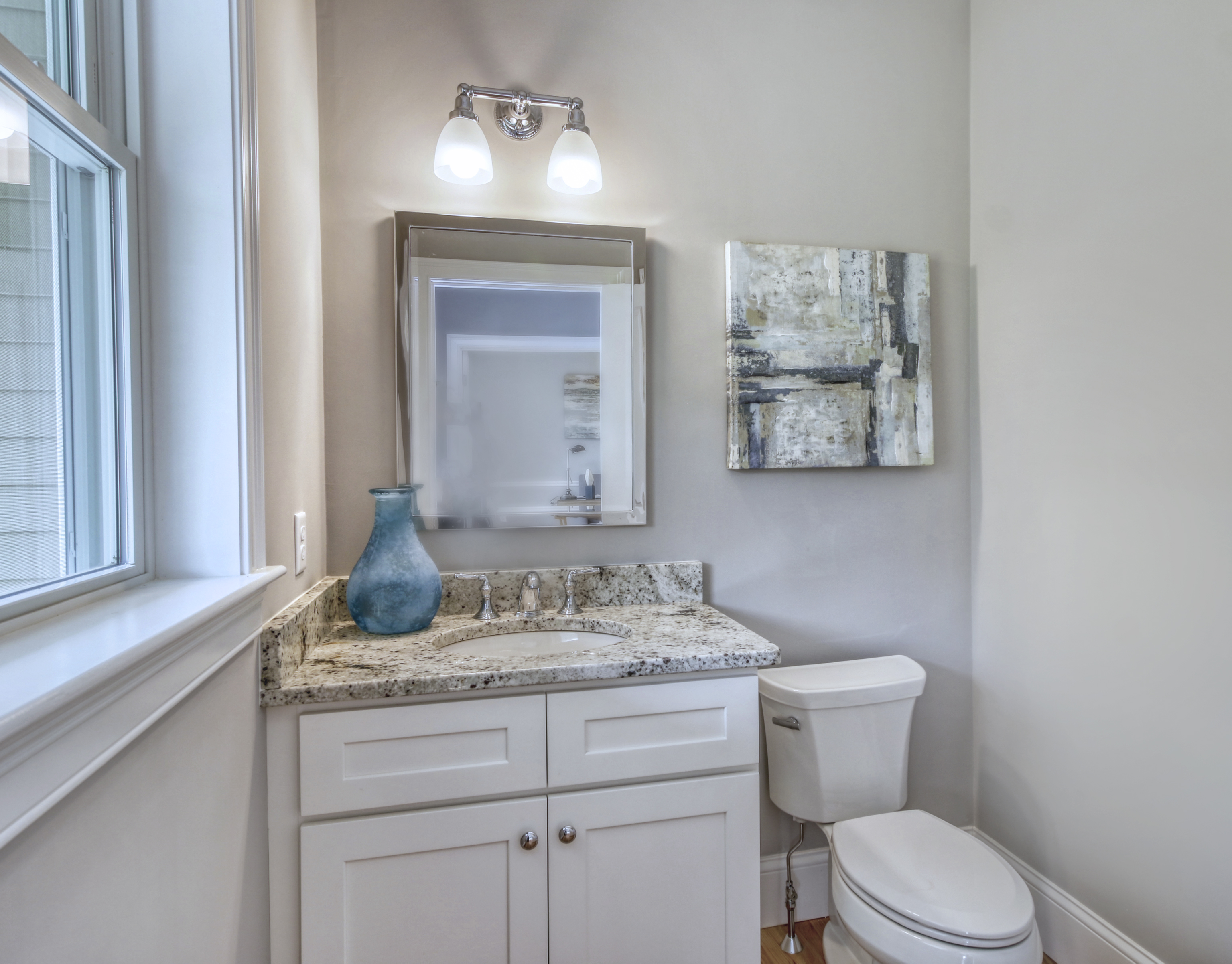 Light grey bathroom walls with a white toilet and sink cabinetry
