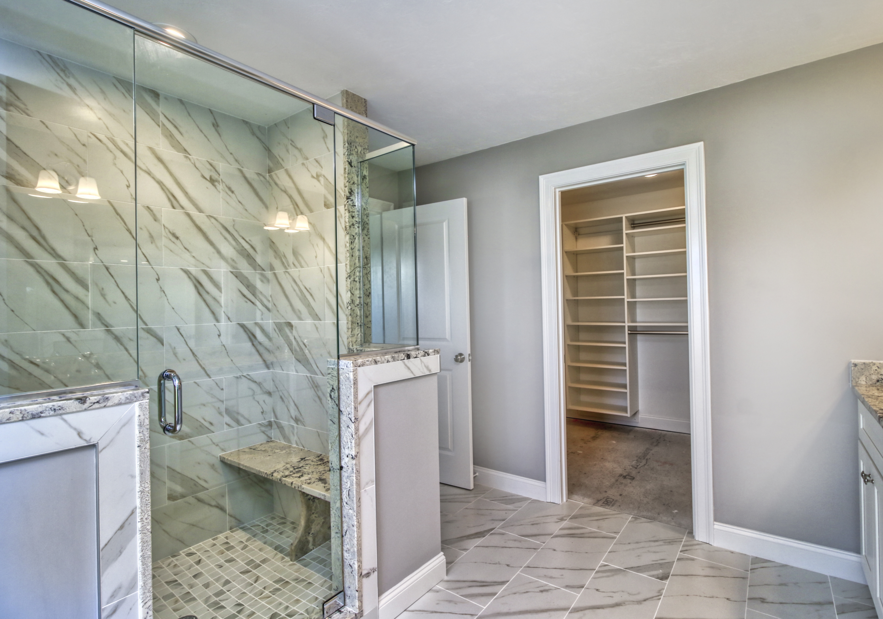 Paste grey bathroom with white accents and glass shower door and walls