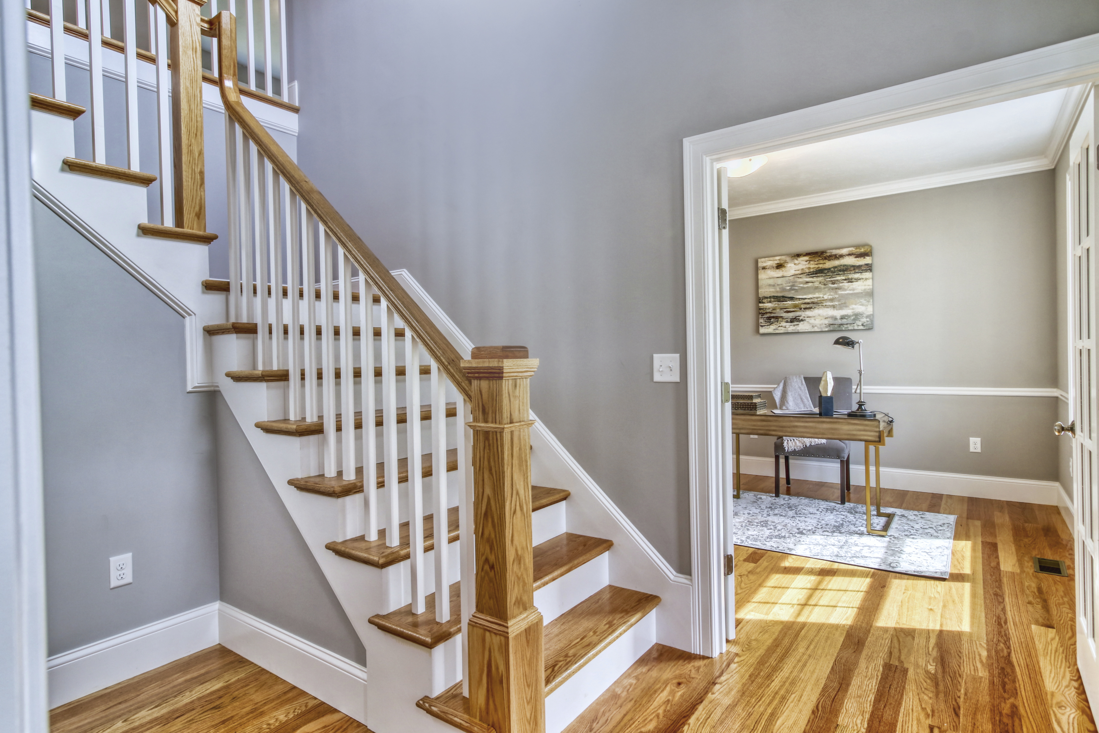 Pastel grey walls with white-and-wood-designed railings and staircase