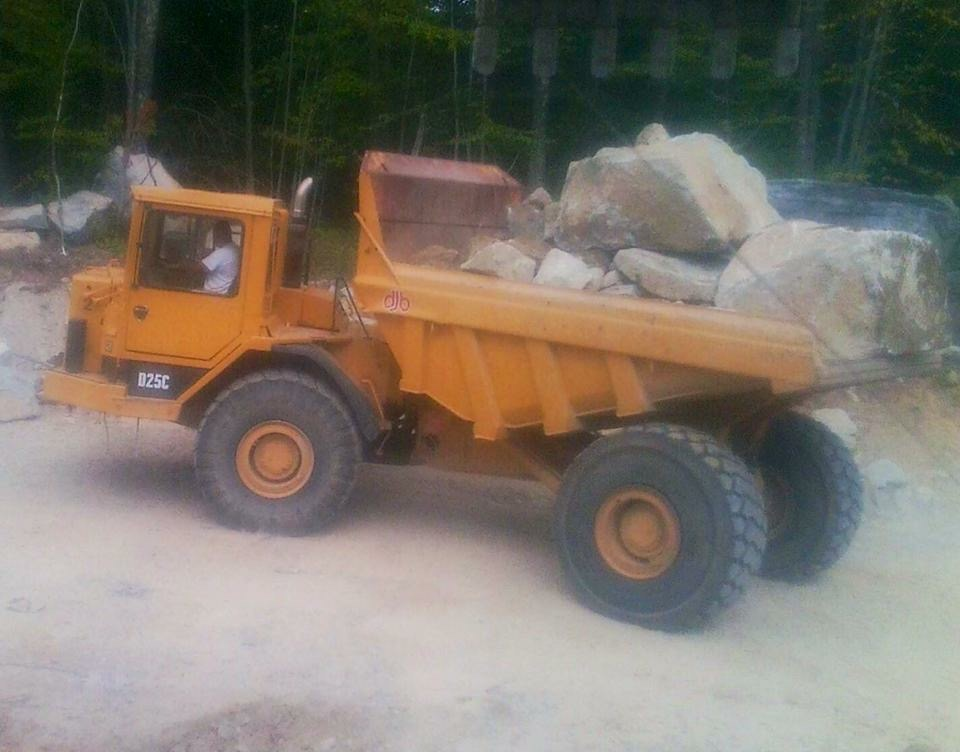 Yellow dump truck filled with big rocks