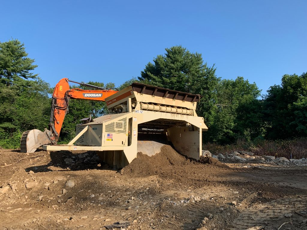 Orange excavator with on-site processing machine