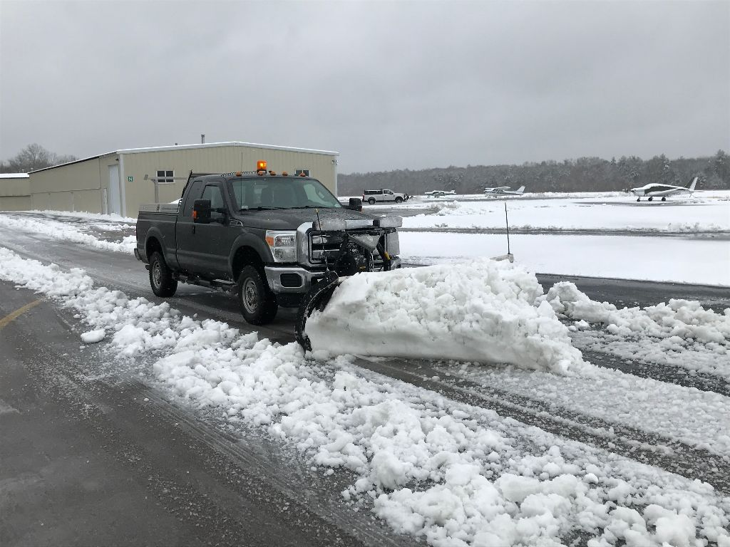 A pickup truck plowing snow on the road