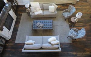 gray couches in the living room with reclaimed hardwood flooring and a fireplace