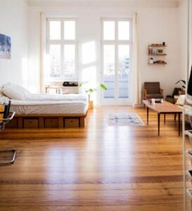 apartment with white walls and hardwood flooring and big windows.