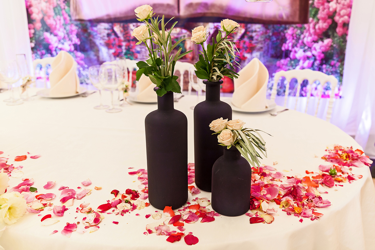 Decor Of Black Bottles With Flowers And Rose Petals For A Weddin