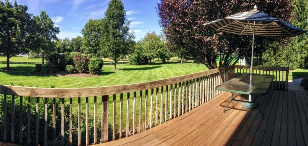 backyard-and-deck-with-table-and-umbrella-on-a-sunny-summer-day_t20_nRByYK