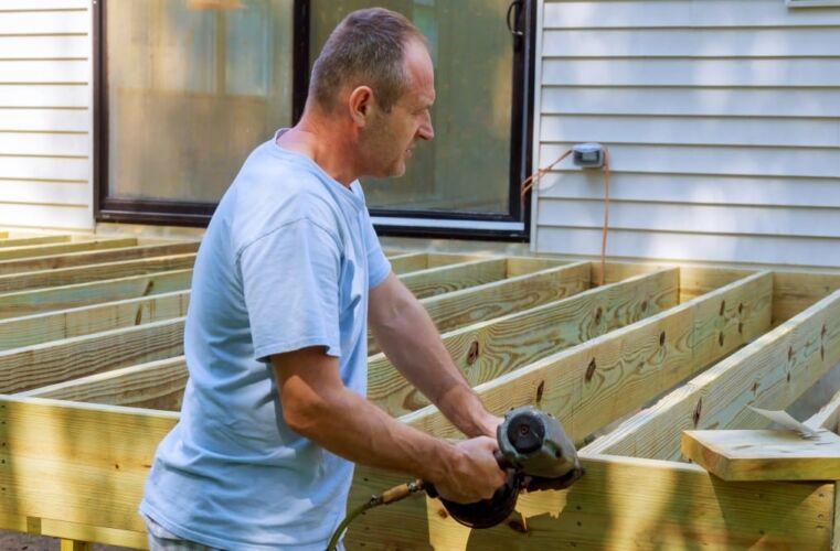 installing-of-wooden-deck-patio-carpenter-hammering-on-a-deck-patio_t20_GgYVZ6