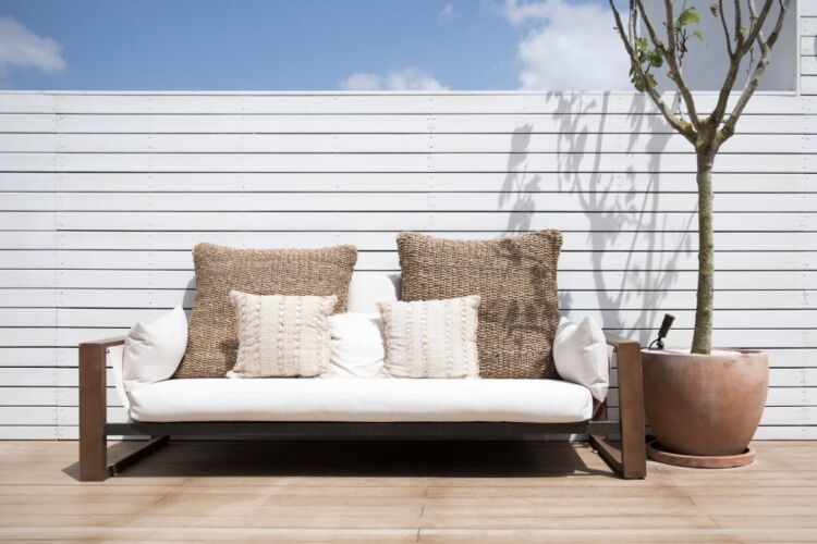view-of-a-modern-simplistic-white-outdoor-sofa-on-a-deck-of-a-house-with-a-lone-tree-in-a-ceramic-pot_t20_6l040N