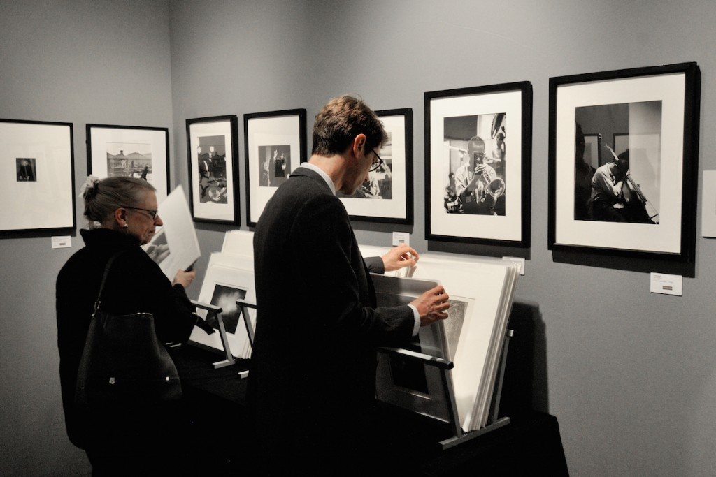 "AIPAD visitors browse through the offering of Michael Dawson Gallery from Los Angeles. Seen here are rare photographs from a series ""Nights in Birdland"" by Carol Reiff, one of the few female jazz photographers working in New York in the 1950s. As a freelance photojournalist, she covered recording sessions, interviews, jam sessions, events and concerts. Right to left are photographs of Paul Chambers and Miles Davis."