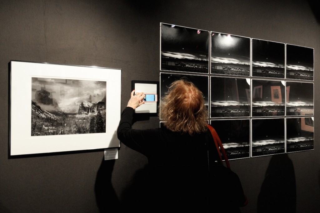 "A woman using her smartphone's camera to capture an AIPAD exhibit reminds us how far photography technology has come over the two centuries of its documented history. Seen here is Scott Nichols Gallery's installation of works by prominent landscape photographer Ansel Adams. On the left is his 1944 photograph of Yosemite National Park titled ""Clearing Winter Storm"". On the right is a series of 12 darkroom artifacts of his famous image ""Moonrise, Hernandez"" that the artist intentionally destroyed with a Wells Fargo check-cancelling machine after realizing they were printed on a defective batch of Ilfordbrom paper. The ""Cancelled Moonrise Artifacts"" series has questionable value but offers us a rare glimpse into Ansel Adams' creative process by illustrating the inconsistencies and difficulties of the photographic process."