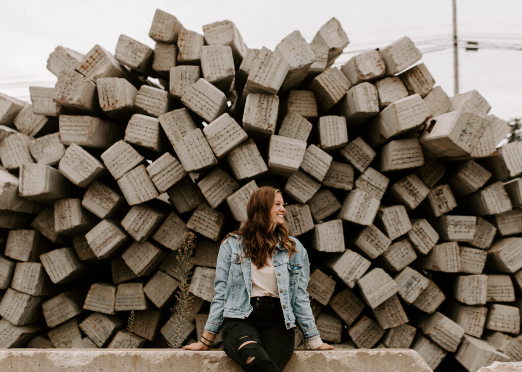 senior sits in front of wood pile at factory and looks to the side