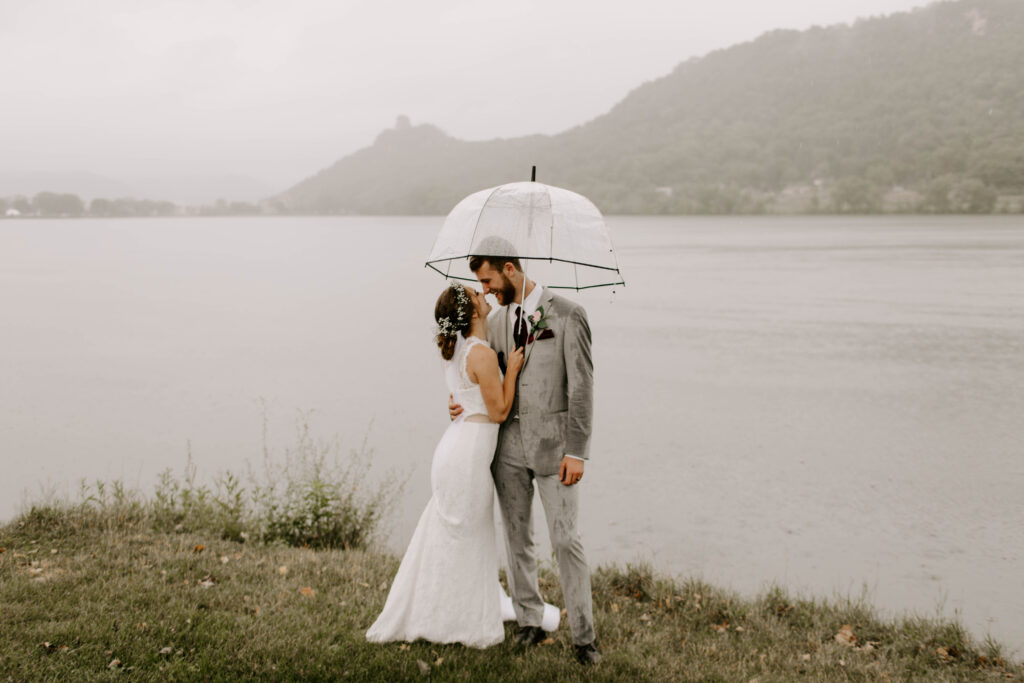 Rainy wedding day, couple snuggles up under umbrella with mountains behind them