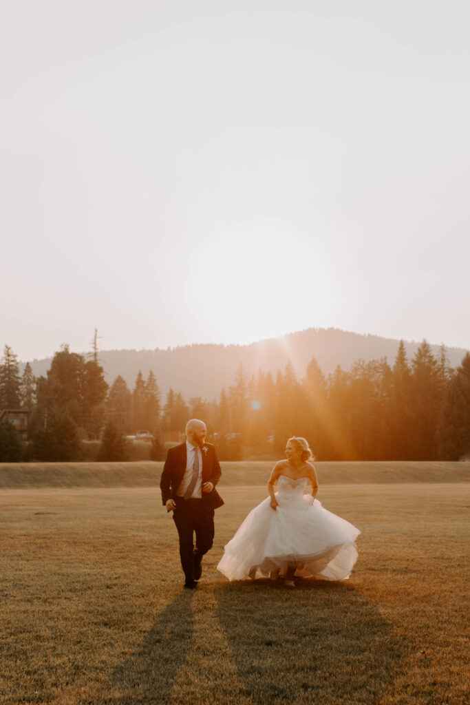 couple runs towards camera with mountains in the background