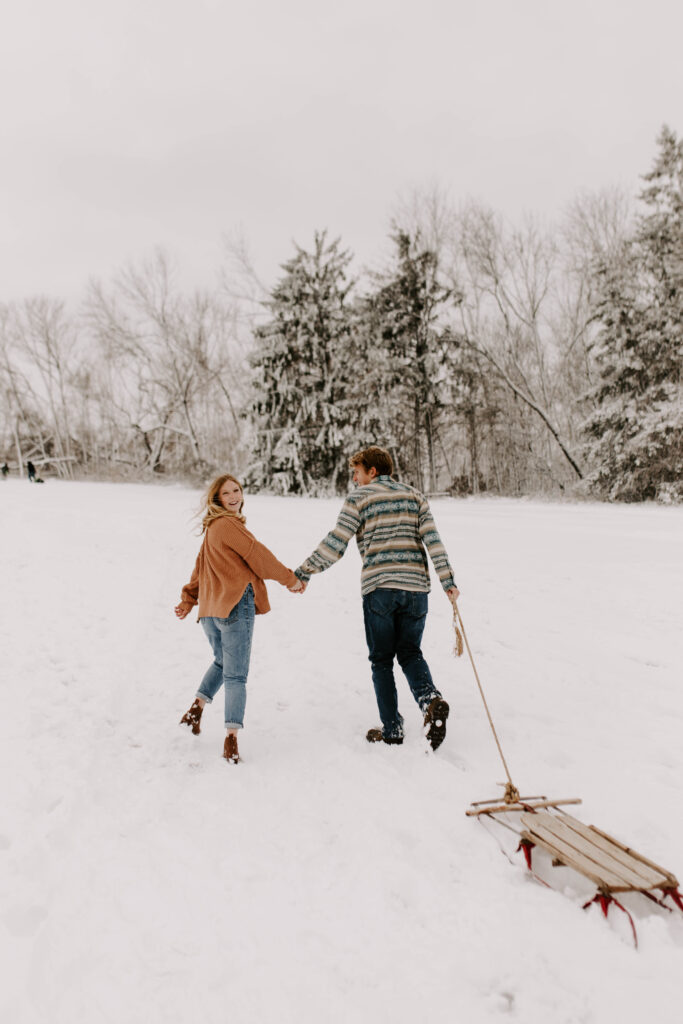 Iowa Wedding Photographer, couple walks up the hill in the snow in December, girl looks back at the camera