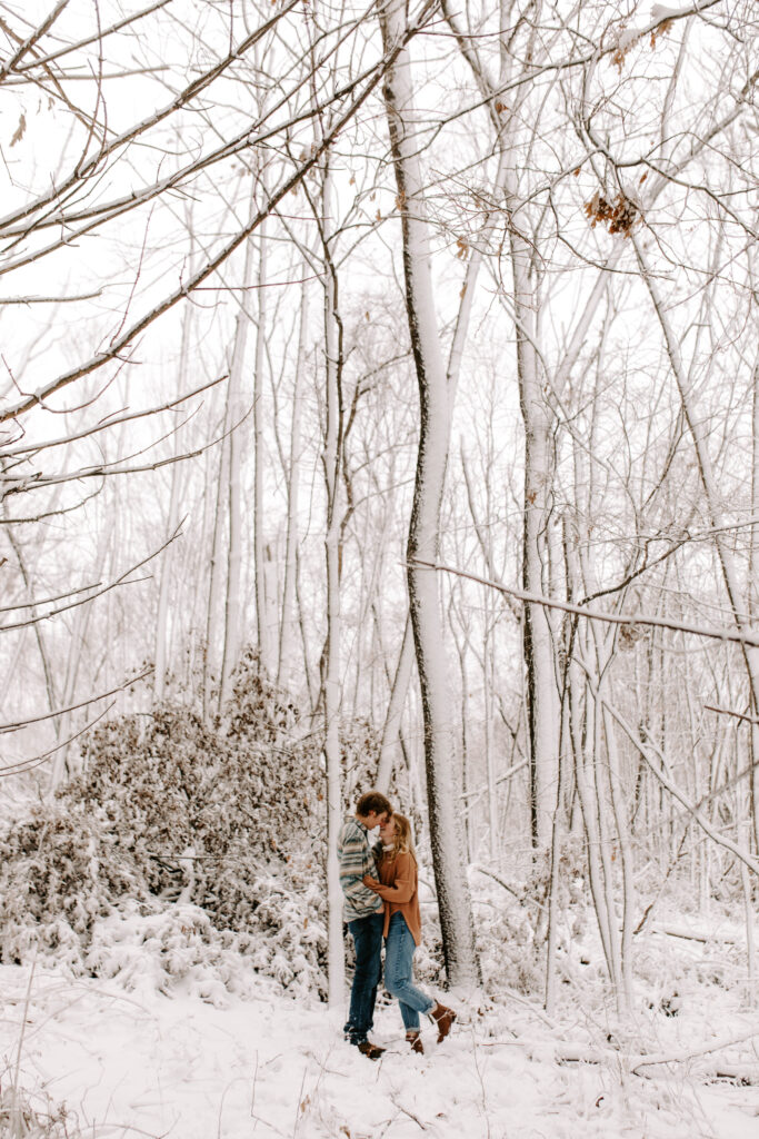 Couple goes in for a kiss in the snow covered woods, Iowa winter engagement photos