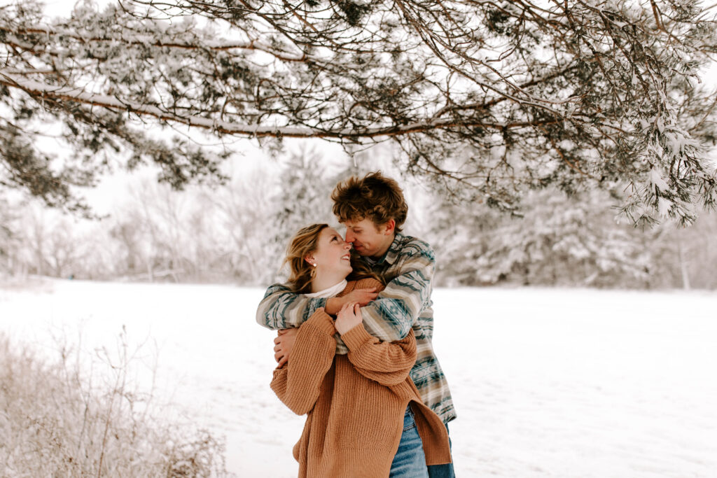 Iowa Wedding Photographer, Couple smiles at each other during their snowy winter engagement session