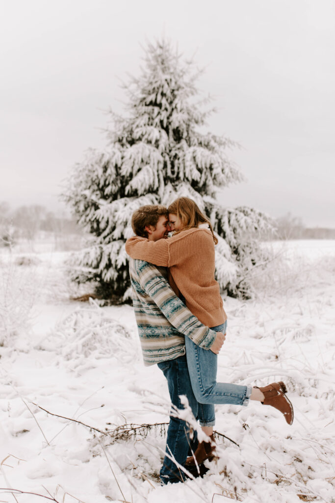 Iowa snowy engagement photos, groom picks up bride and kisses her in front of snow covered tree
