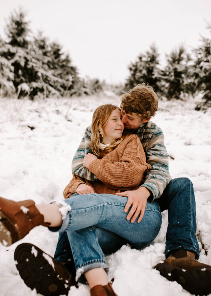 couple sits in the snow together snuggled together