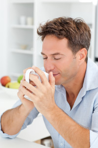 Handsome man smelling his coffee sitting in his kitchen