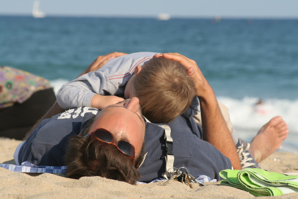 Niño durmiendo sobre su padre en la playa