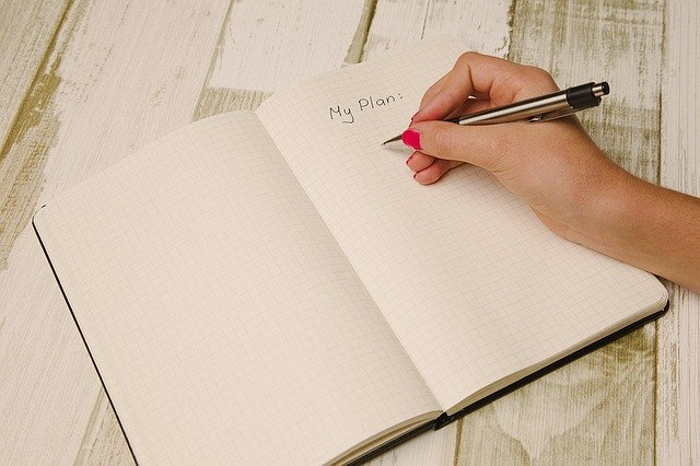 Woman's hand writing on a blank notebook page