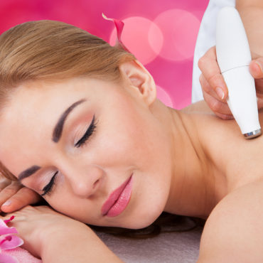 Relaxed young woman receiving microdermabrasion therapy at beauty spa