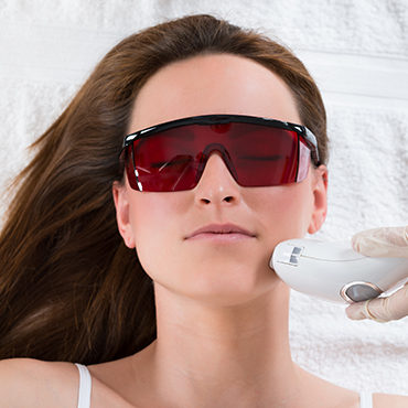 Young Woman Receiving Epilation Laser Treatment On Face At Beauty Center