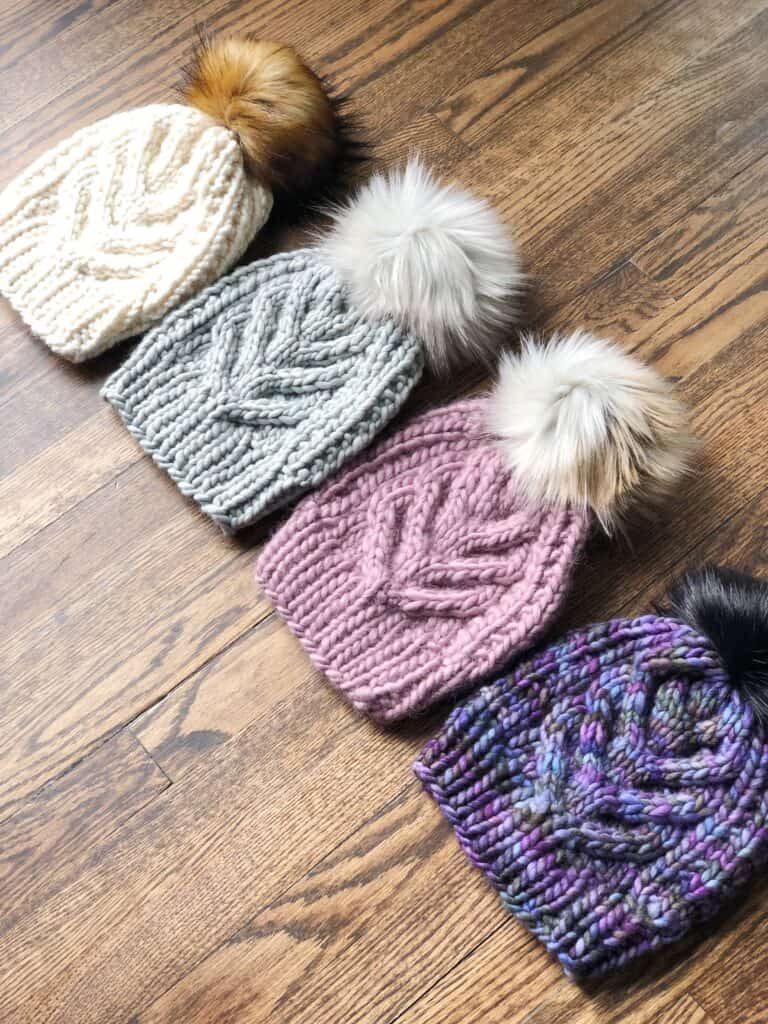 Staghorn cable knit hats with faux fur pom poms