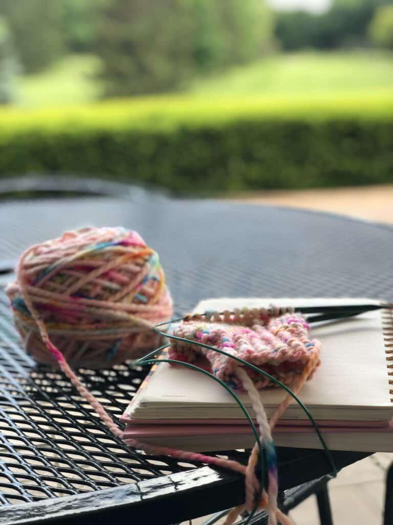 Knitting pattern writing while kids are golfing.