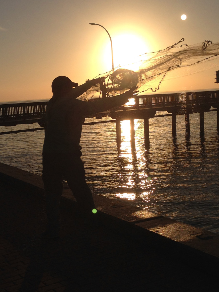 Local fisherman casting for bait on the Fairhope City Pier at sunset