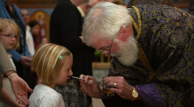 Father John Troy Mashburn annointing parishioners with holy oil during Unction at St. John Orthodox Church.