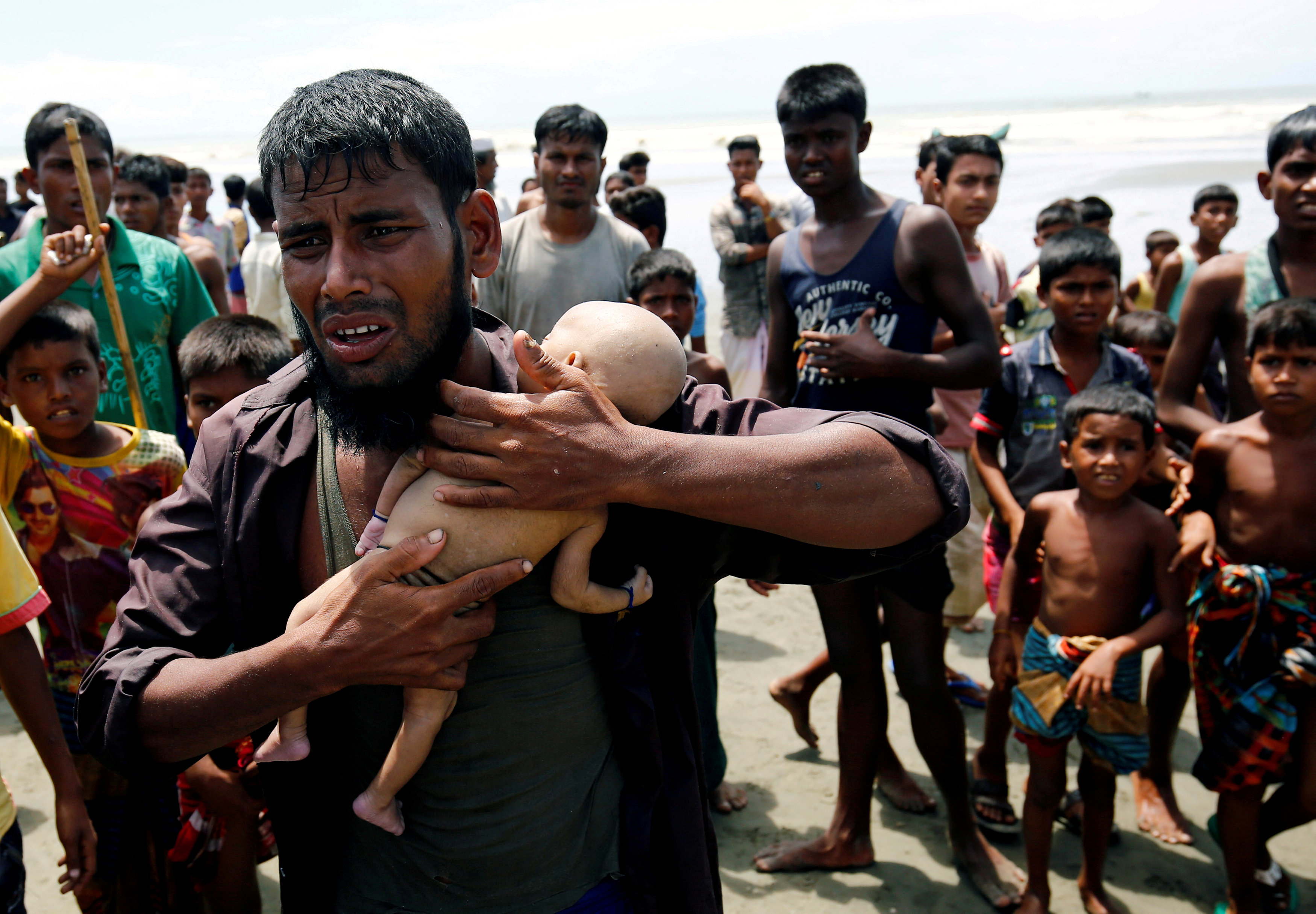 Nasir Ahmed, a Rohingya refugee man cries as he holds his 40-day-old son, who died as a boat capsized in the shore of Shah Porir Dwip while crossing Bangladesh-Myanmar border, in Teknaf