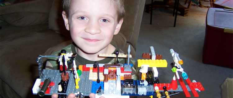 Young boy proudly showing off his lego creation