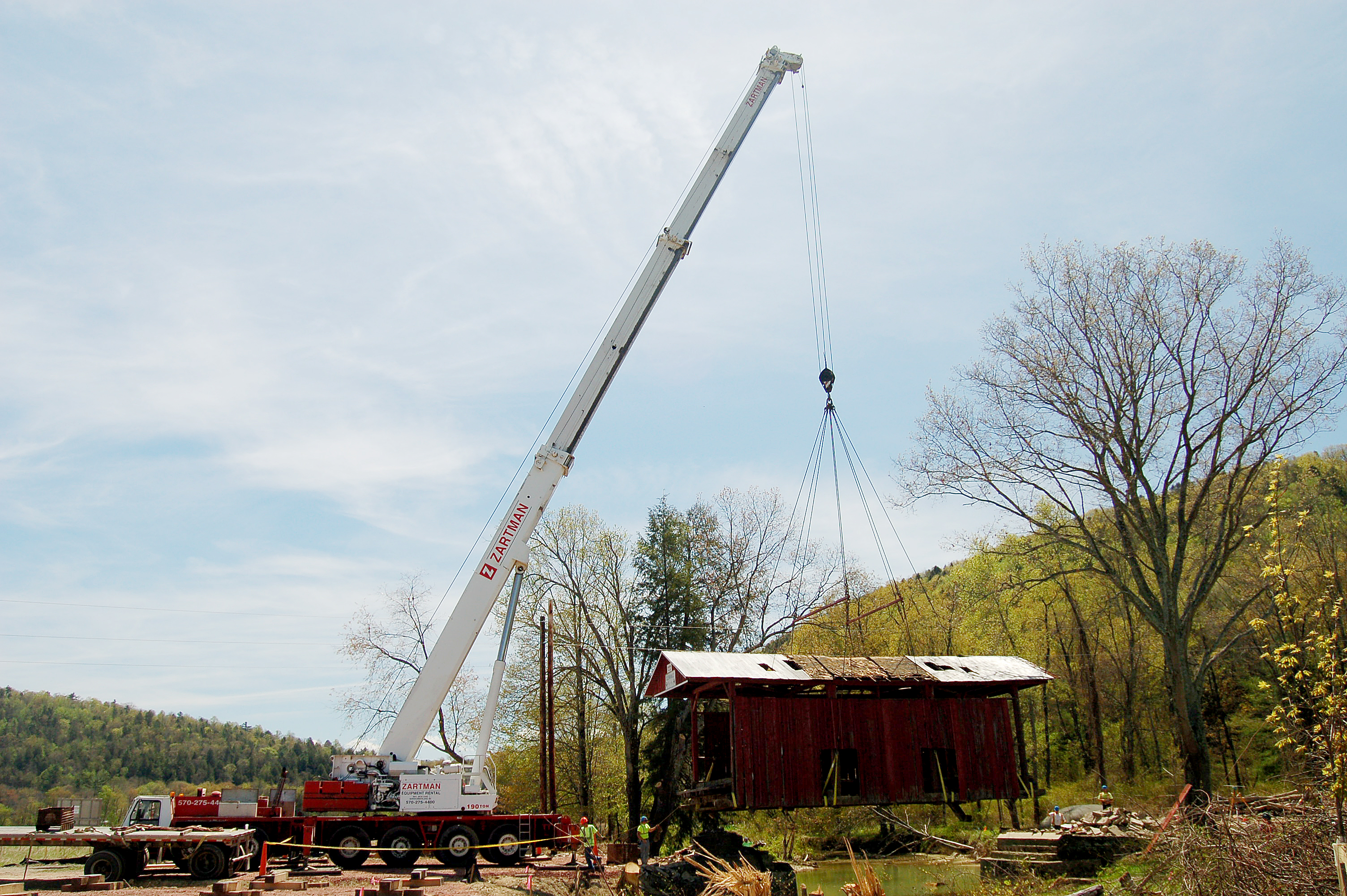 A covered bridge is lifted off its supports and placed on a trailer bed.