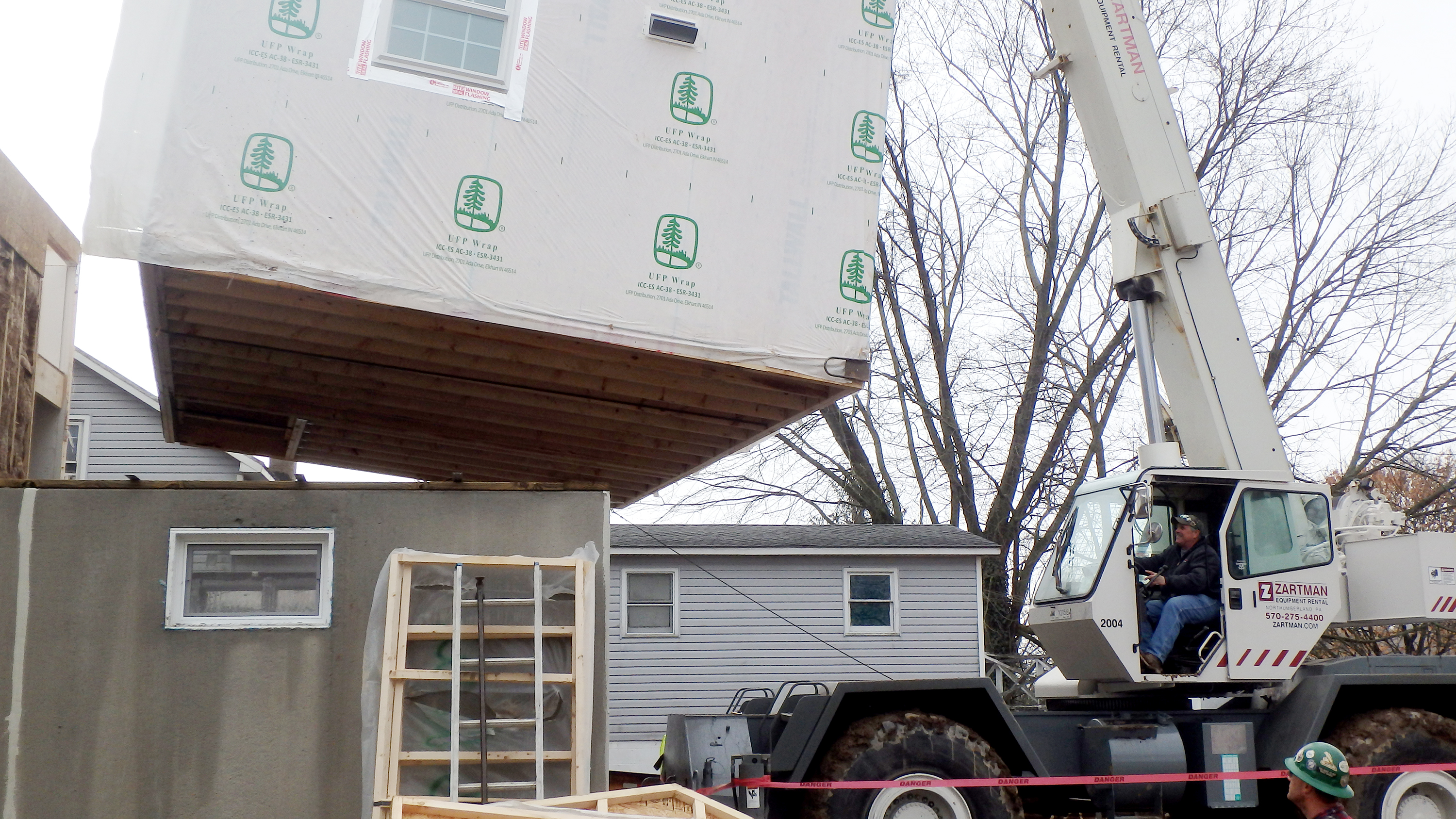 A section of modular home is set into place.