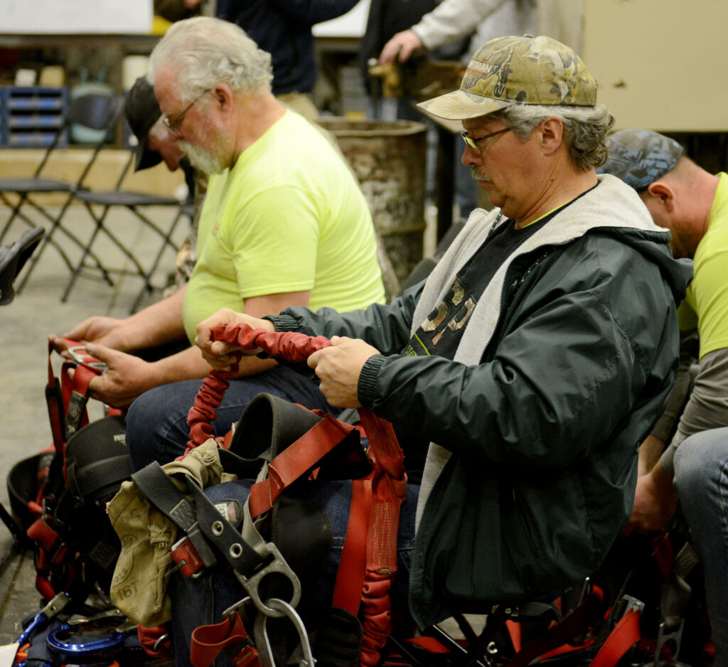 Myron Yoder and Dennis Kuczynski inspect fall protection harnesses during Zartman Construction's safety training.