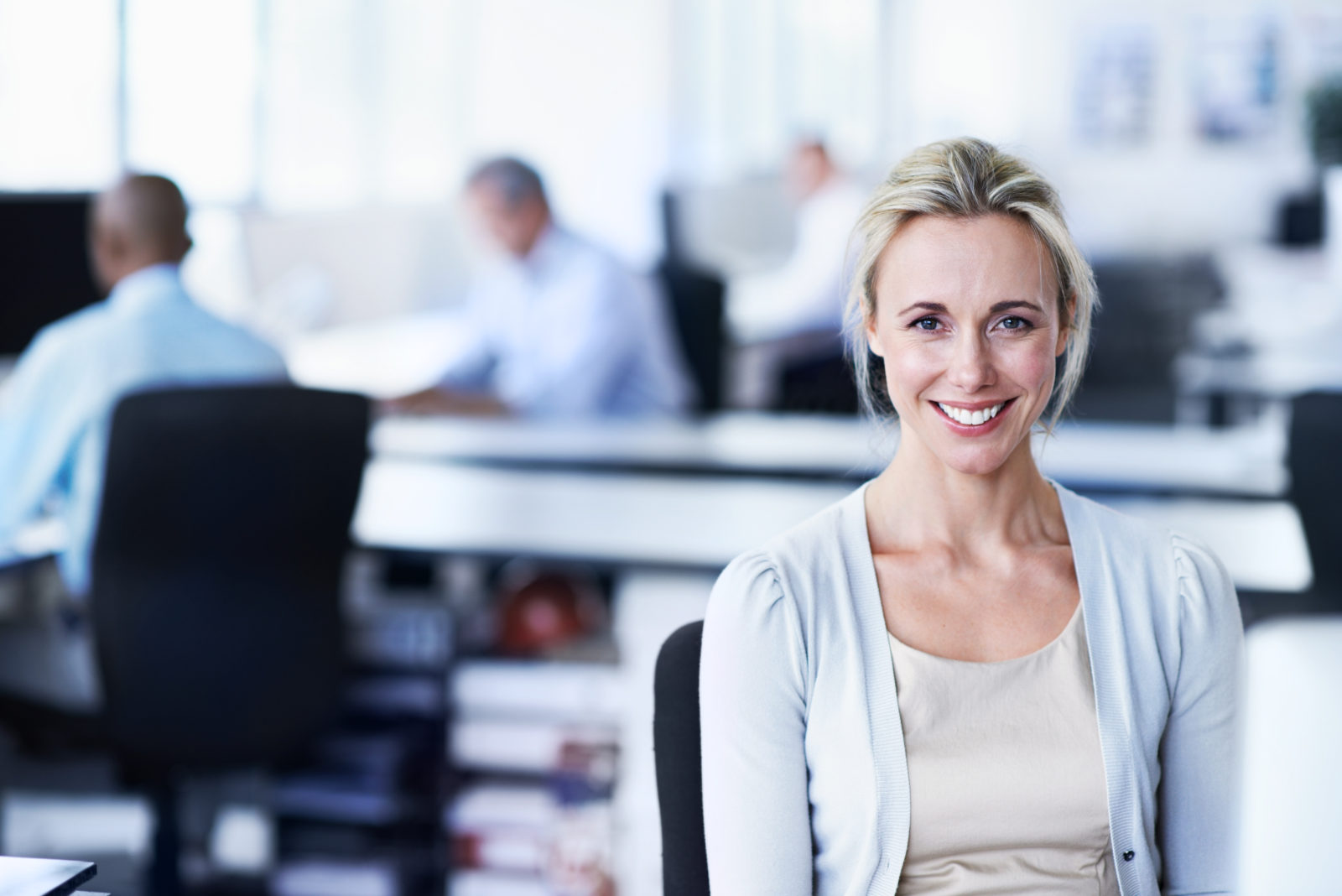 Shot of a woman working sitting in an office with colleagues in the backgroud