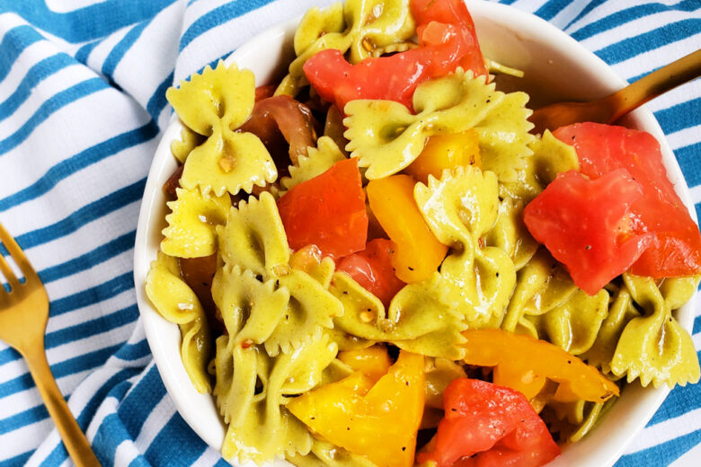 Easy Heirloom Tomato Bow-Tie Pasta with spinach bow-tie pasta in a white bowl on a blue and white striped towel