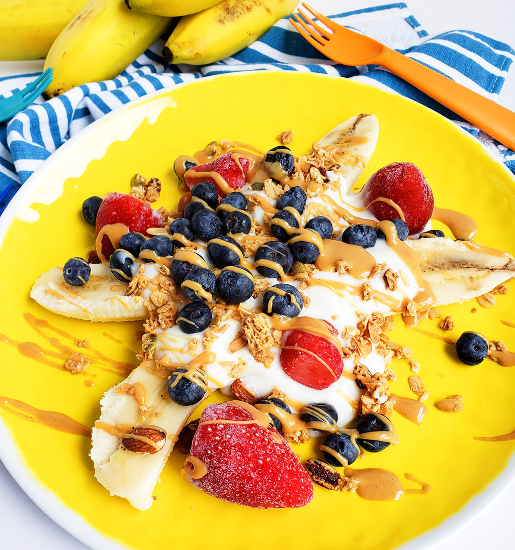 Healthy Breakfast Banana Split, banana sliced in half topped with Greek yogurt, blueberries, strawberries, granola, and peanut butter drizzle on a yellow plate