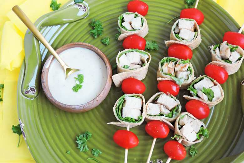 Mini Chicken Caesar Salad on a wooden skewer with cherry tomatoes
