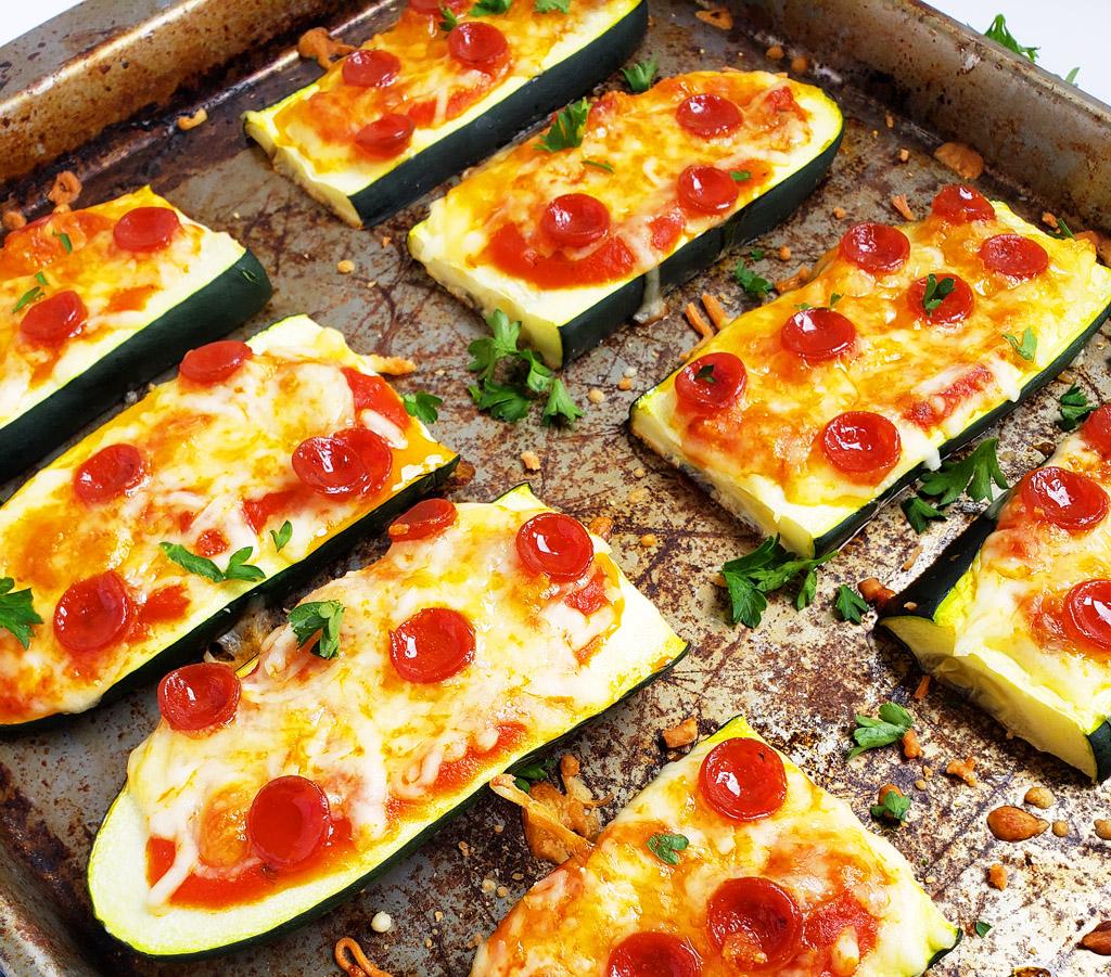 Mini Zucchini Pizza Boats, sliced zucchini topped with mozzarella cheese and mini pepperoni on a cookie sheet