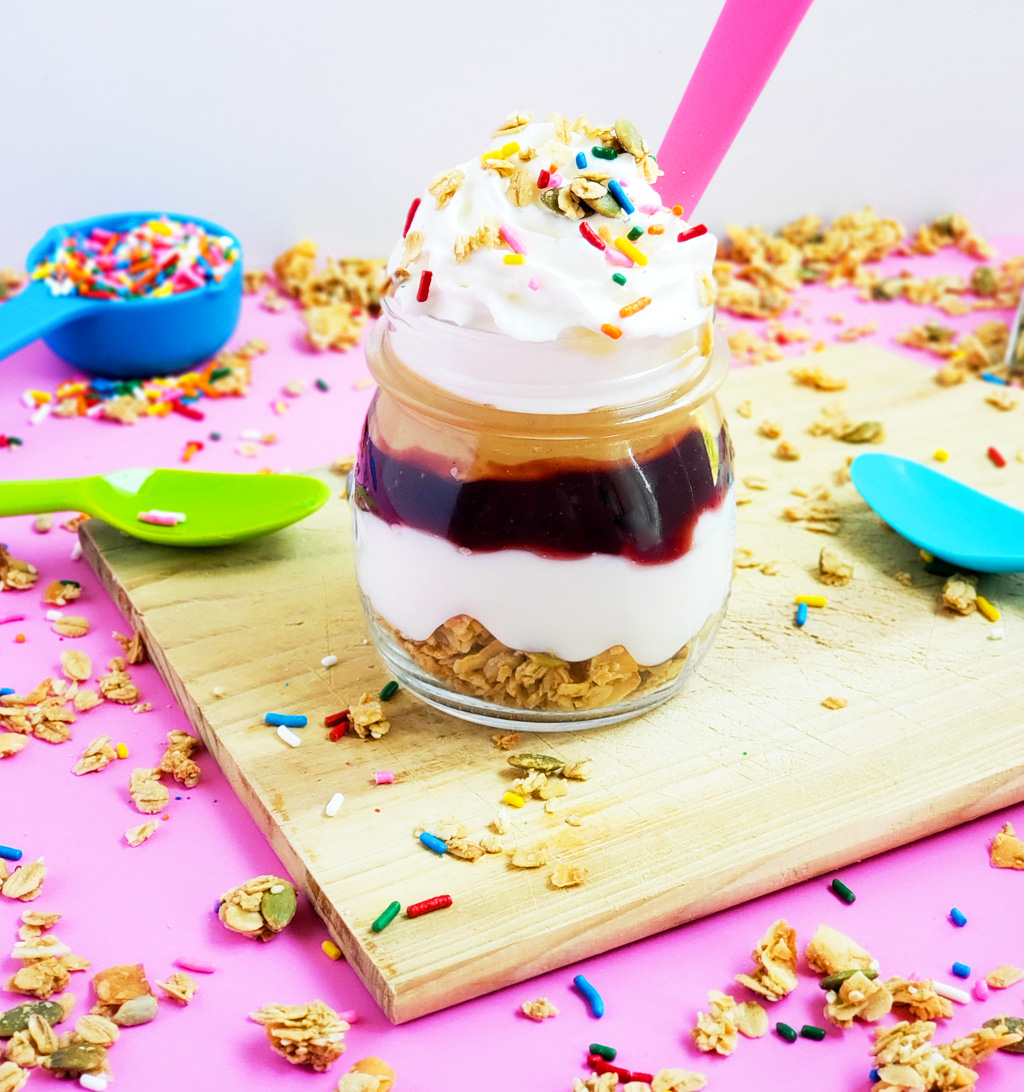 PB&J Greek Yogurt Parfait made with Bob's Red Mill Granola, peanut butter and jelly and sprinkles on a pink surface