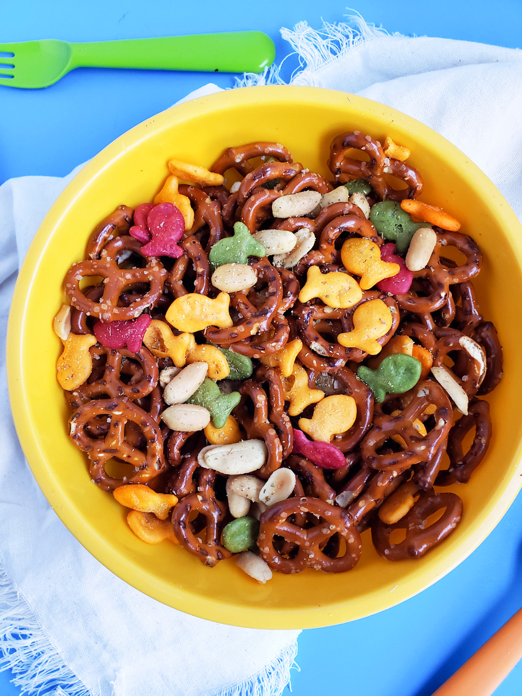 CJs Rockstar Trail Mix made with multi-colored goldfish crackers, pretzels, and peanuts in a yellow bowl on a blue surface