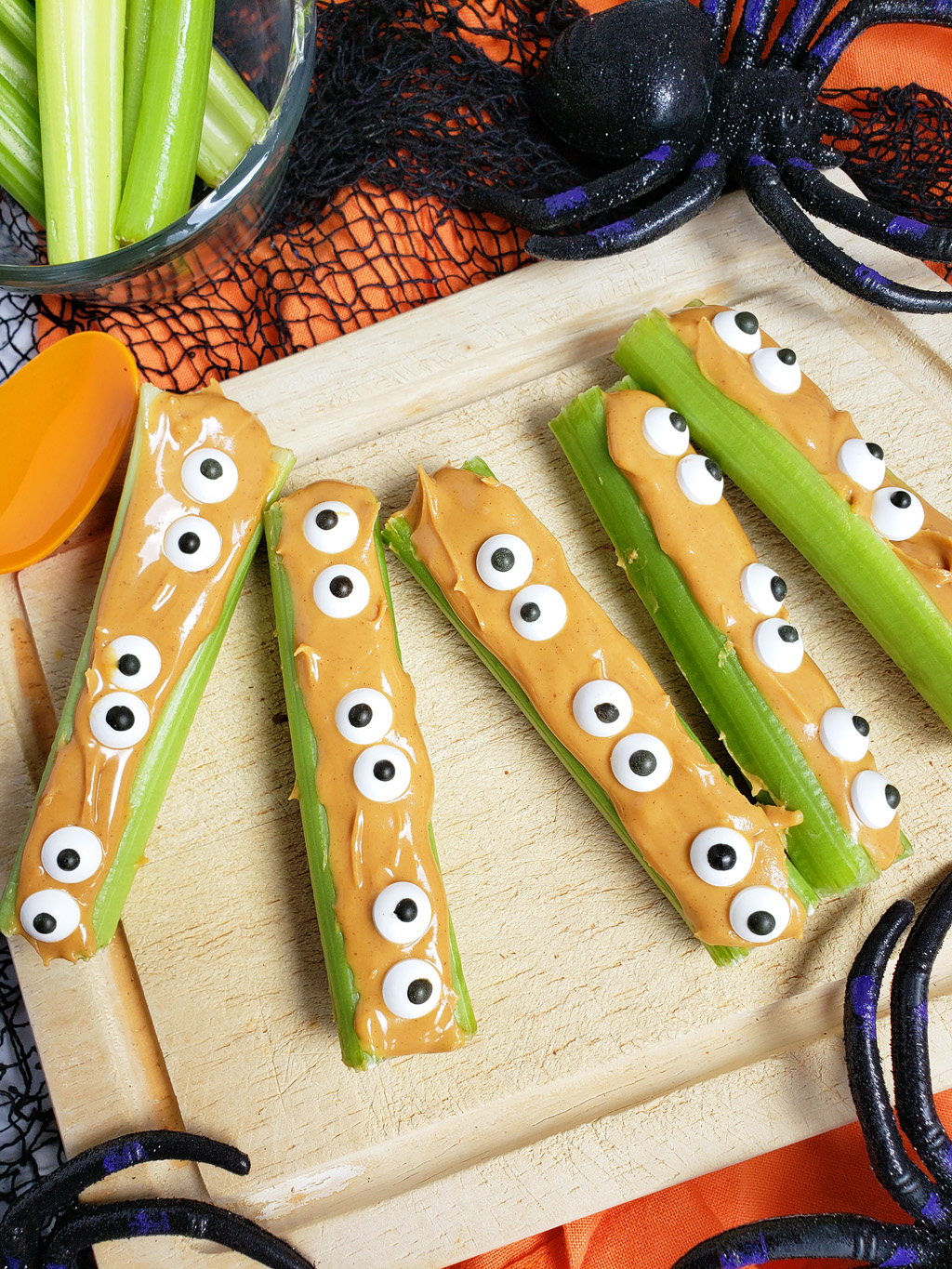 spooky monsters on a log made with celery sticks, peanut butter and candy eyes