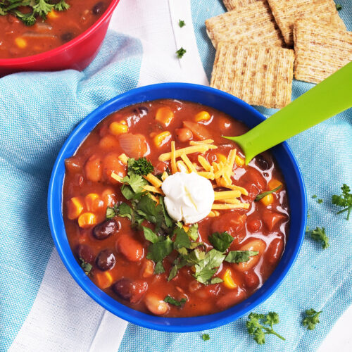 Simple Vegetarian Taco Soup, the perfect meatless meal, topped with green onion, cheese, and sour cream, served in a kid-friendly blue bowl with a green spoon. #tacosoup #vegetarianmeals #plantbasedkids #plantbasedmeals #plantbasedkidmeals